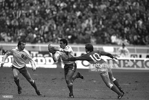 Philippe Sella of France supports team mate Serge Blanco as Paul Turner of Wales tackles him during the Five Nations match at Cardiff Arms Park in...
