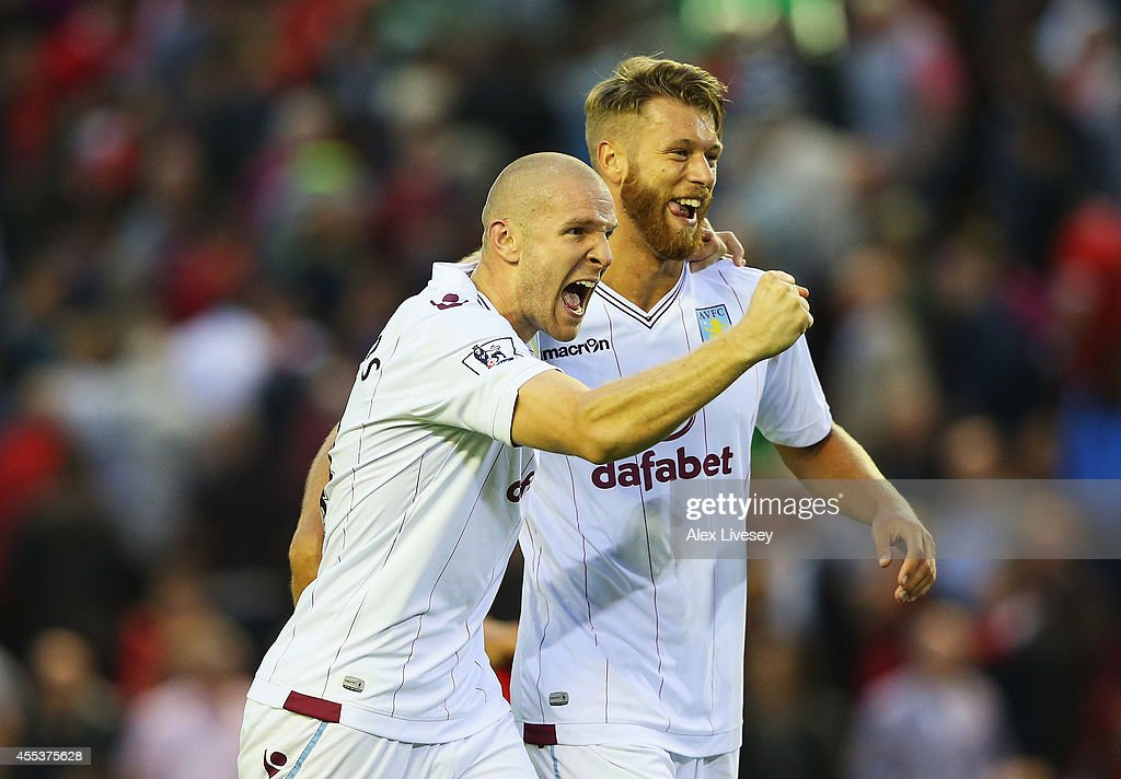 Philippe Senderos (L) of Aston Villa celebrates victory with Nathan Baker after the Barclays Premier League match between Liverpool and Aston Villa at Anfield on September 13, 2014 in Liverpool, England.
