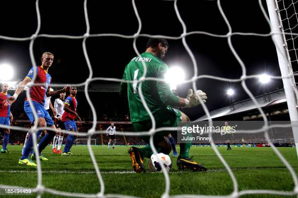 Philippe Senderos of Fulham squeezes the ball through the legs of goalkeeper Julian Speroni of Crystal Palace to score his team's fourth goal during...
