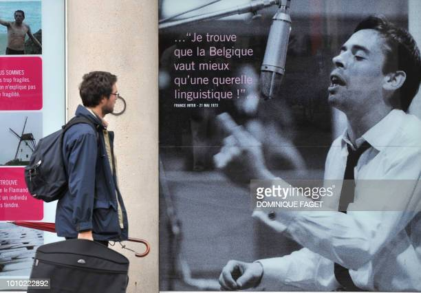 Philippe SIUBERSKI Pedestrians walk past a poster announcing on October 02 2008 in Brussels the exhibition J'aime les Belges about Belgian singer...