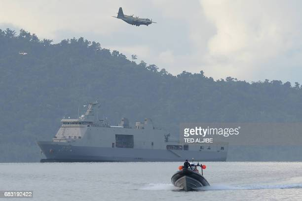 A Philippine air force C130 cargo plane flies over Philippine navy sea lift vessel BRP Tarlac while a speed boat loaded with US and Philippine...