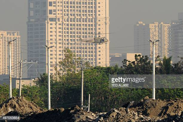 Philippine Air Force helicopter flies next to buildings during a security dry run near the site of the Asia-Pacific Economic Cooperation summit as...