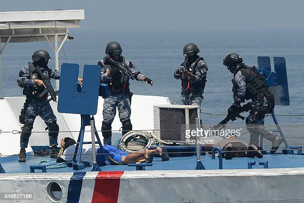 Philippine and Japanese Coast Guard personnel conduct a drill on board a Philippine Coast Guard boat during their annual antipiracy exercise in the...