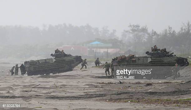 Philippine and US marines take their position next to Amphibious Assault vehiclle during a beach landing as part of the PhilippinesUS amphibious...