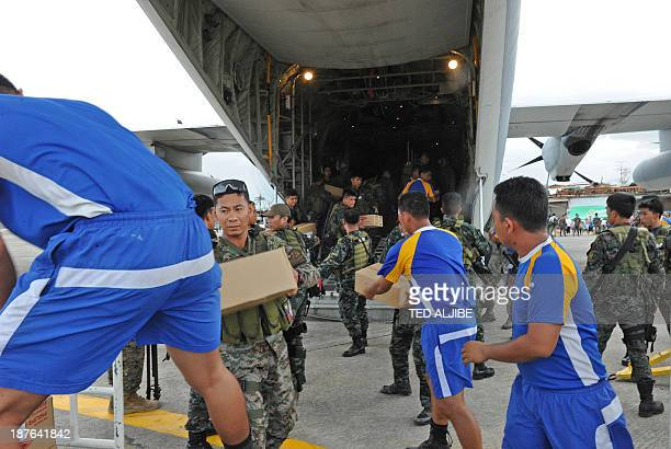 Philippine and US military personnel unload relief goods from a US military C-130 plane at Tacloban airport in the central Philippines on November 11...