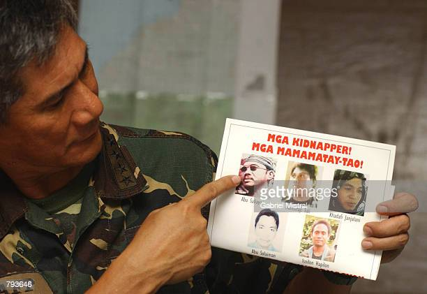 Philippine Armed Forces Chief of Staff Roy Cimatu points to a photo of Abu Sayyaf leader Abu Sabaya during a media conference at the southern command...
