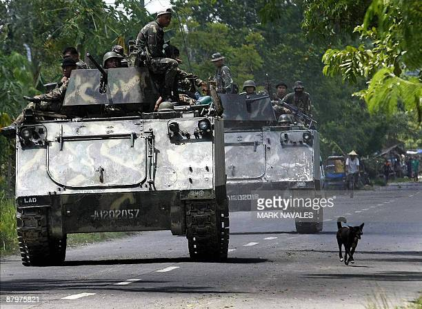Philippine Army armoured personnel carriers and trucks move down a highway of the town of Datu Piang after separatist Moro Islamic Liberation Front...