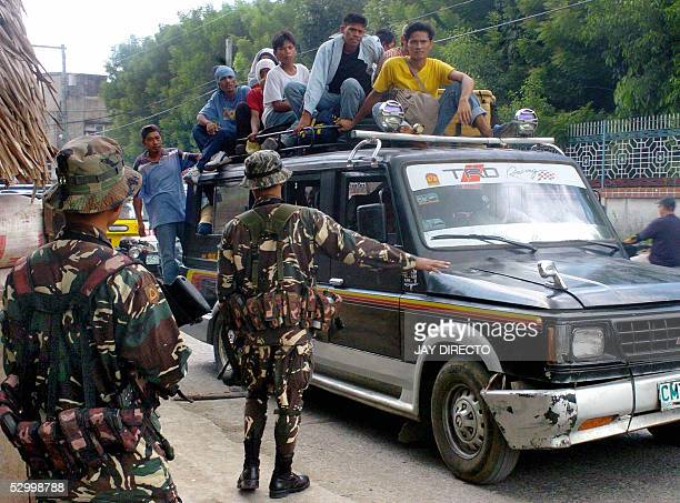 Philippine Army soldiers inspect a vehicle full of passengers on the outskirts of Cotabato in the southern Philippines where separatist Moro Islamic...