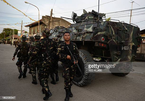 Philippine army troops take cover next to an armored personnel carrier before taking position during a standoff with Muslim gunmen in Zamboanga City...