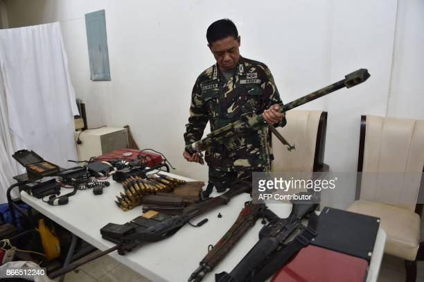 Philippine army's Colonel Romeo Brawner deputy commander of Task Force Ranao inspects a homemade barrett sniper and other weapons recovered from...