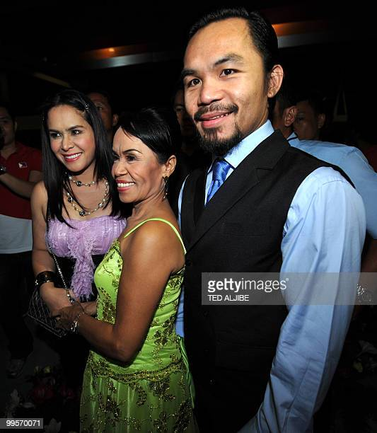 Philippine boxing superstar Manny Pacquiao poses for a photo with his mother Dionesia and wife Jinkee during his victory party after winning a seat...