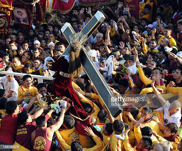 Philippine Catholic pilgrims try to reach for the statue of the Black Nazarene a lifesize icon of Jesus Christ carrying a cross at the start of the...