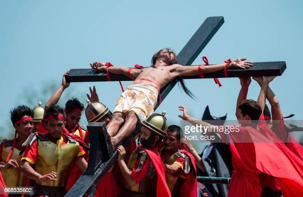 A Philippine Christian devotee reacts in pain while nailed to a cross during a reenactment of the Crucifixion of Christ during Good Friday...
