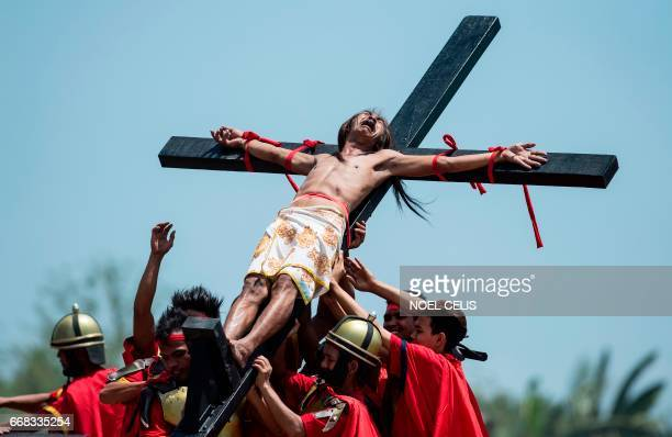 Philippine Christian devotee reacts while nailed to a cross during a reenactment of the Crucifixion of Christ during Good Friday celebrations ahead...