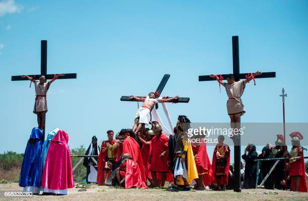 Philippine Christian devotee Ruben Enaje is lowered to the ground after he was nailed to a cross during a reenactment of the Crucifixion of Christ...