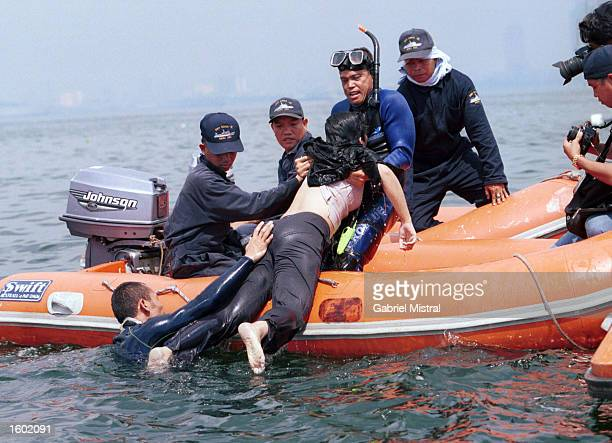 Philippine Coast Guard divers recover one of the passengers from a Fokker 27 plane that crashed into Manila Bay shortly after takeoff November 11...