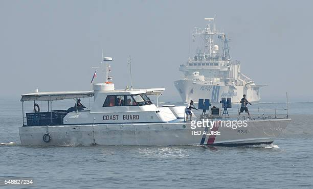 Philippine Coast Guard personnel as mock pirates are seen aboard their boat while Japanese Coast Guard ship PLH02 Tsugaru steams towards them during...