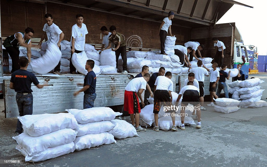 Philippine Coast Guard personnel carry relief goods for victims of Typhoon Bopha in New Bataan, Compostela Valley in the southern Philippines, on board a ship in Manila on December 6, 2012. A quarter million people were homeless and 477 confirmed dead after the Philippines' worst typhoon this year, officials said Thursday, as the government appealed for international help. Typhoon Bopha ploughed across Mindanao island on Tuesday, flattening whole towns in its path as hurricane-force winds brought torrential rain that triggered floods and landslides.