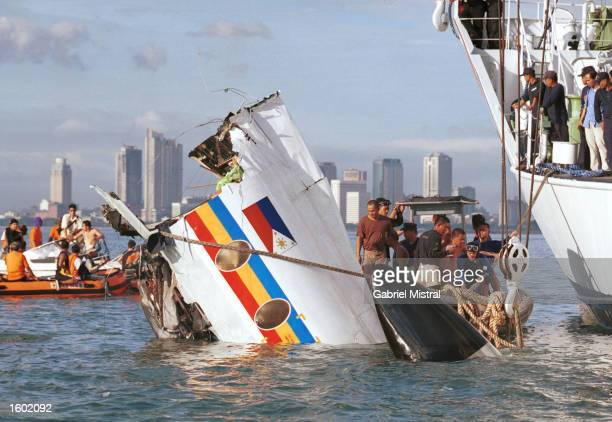 Philippine Coast Guard personnel observe as the forward portion of a plane is lifted from the water November 11 2002 in Manila Philippines The Fokker...