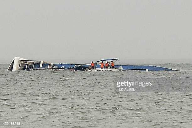 Philippine coast guard personnel on a boat inspect a small ferry that capsized at the height of Typhoon Kalmaegi along Manila bay on September 15...