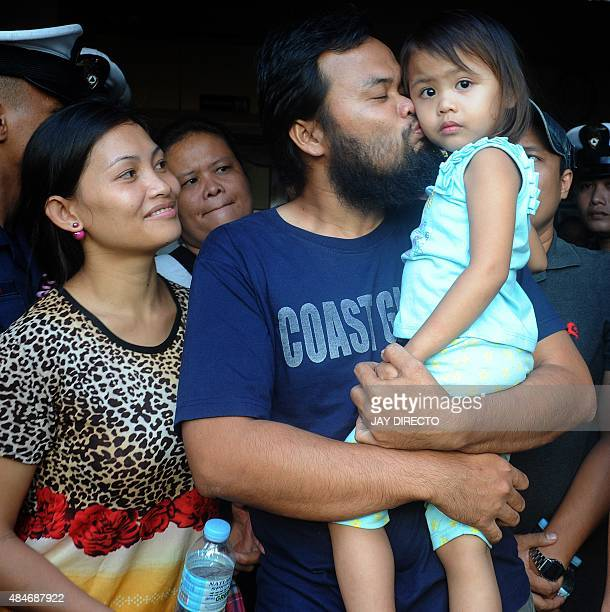 Philippine coastguard Rod Allain Pagaling carries his daughter Allian with wife Judith as he is reunited with his family in Manila on August 21 2015...