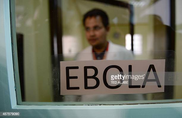 A Philippine doctor inspects an isolation room for Ebola patients during a press conference by health officials on the country's preparedness against...