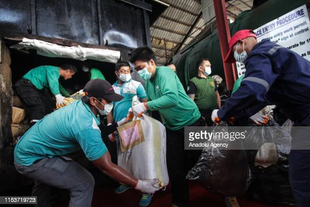 Philippine Drug Enforcement Agency personnel load seized illegal drugs into an incinerator for destruction at a waste facility in Trece Martires...
