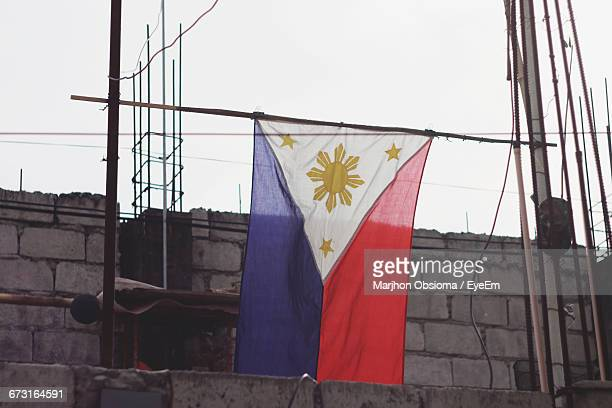 philippine flag hanging on incomplete building against sky - filipino flag stock pictures, royalty-free photos & images