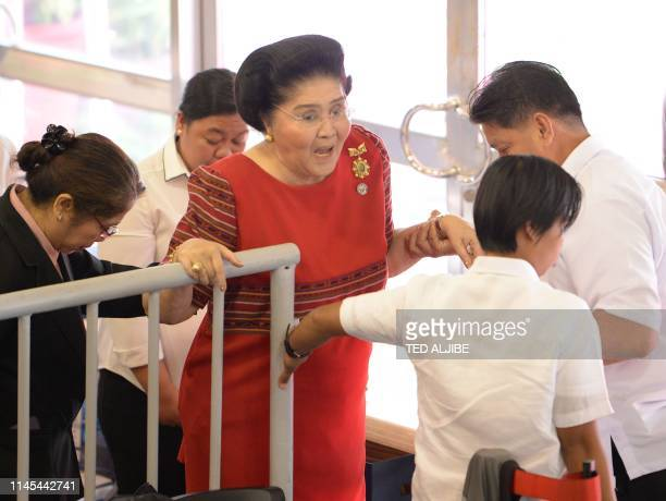 Philippine former first lady Imelda Marcos is helped by aides as she leaves after attending the proclamation of her daughter Senator Imee Marcos in...