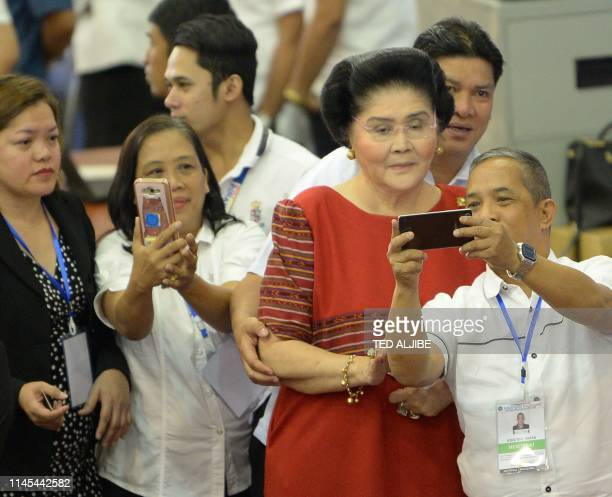 Philippine former first lady Imelda Marcos poses for photos with election commission on election employees after attending the proclamation ceremony...