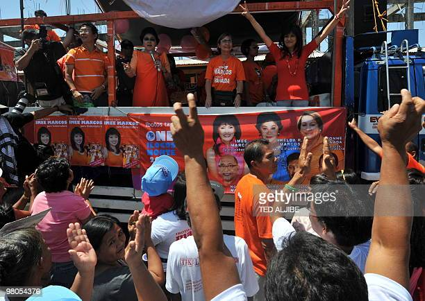 Philippine former first lady Imelda Marcos speaks while her daughter Imee who is runing for governor flashes the victory sign during a campaign...