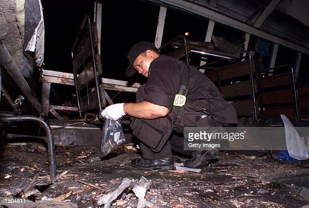 Philippine investigator inspects the interior of a bus after a bomb exploded at the rear of the bus October 18 2002 in Manila The bomb destroyed the...