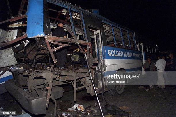 Philippine investigators inspect the interior of a bus after a bomb exploded at the rear of the bus October 18 2002 in Manila The bomb destroyed the...