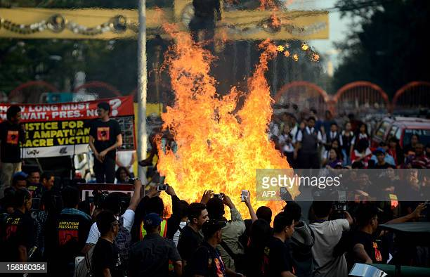 Philippine journalists and students burn an mock bulldozer at the Malacanang Palace in Manila on November 23 to commemorate the third anniversary of...