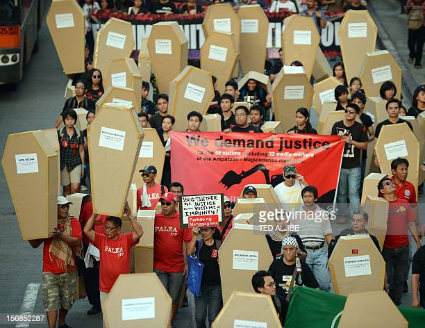Philippine journalists and students carry mock coffins as they march towards Malacanang Palace in Manila on November 23 to commemorate the third...