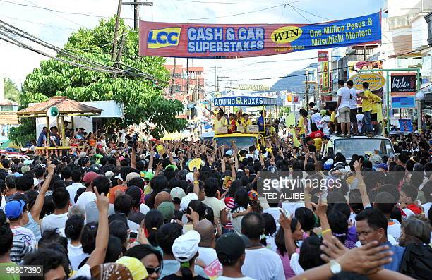 Philippine Liberal Party presidential candidate Benigno Aquino and runningmate Mar Roxas distribute yellow wristbands to crowds of supporters during...