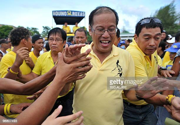 Philippine Liberal Party presidential candidate Benigno Aquino is greeted by supporters as he goes to board his helicopter during a campaign sortie...