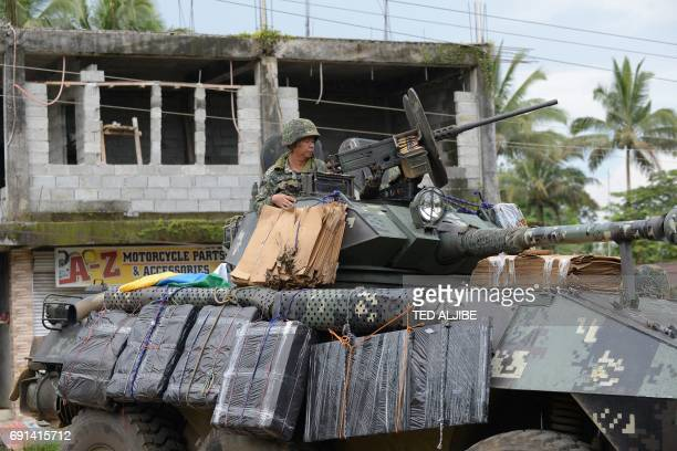 A Philippine marine sits atop a V300 light wheeled armoured vehicle with padded carboard destroyed after it was hit by an RPG after engaging Islamist...