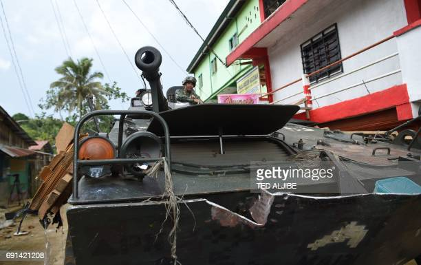 A Philippine marine sits atop their V300 light wheeled armoured vehicle hit by an RPG after engaging Islamist militants in Marawi on the southern...