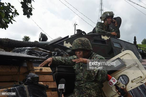 A Philippine marine sitting atop their V300 light wheeled armoured vehicle gestures as he relates how they engaged Islamist militants in Marawi on...