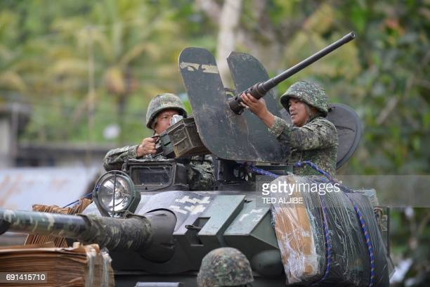 Philippine marines adjust the barrel of their 50mm machine gun atop their V300 light wheeled armoured vehicle with padded carboard after engaging...