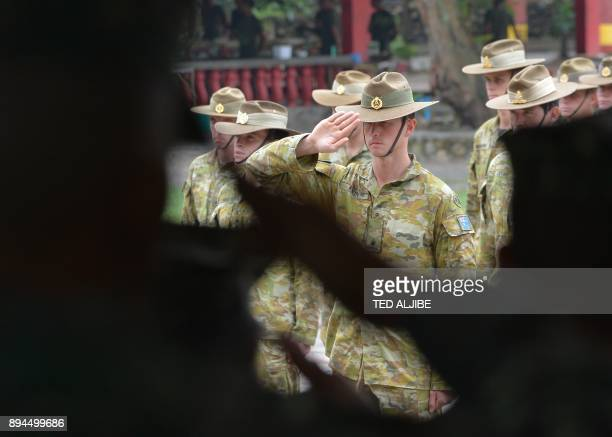 Philippine Marines and Australian soldiers salute during the closing ceremony of the Military Operation Urbanized Terrain training exercises at the...