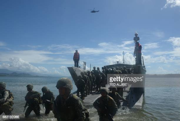 Philippine marines disembark from their landing ship as security responders during a simulation of a disaster drill as part of the annual joint...