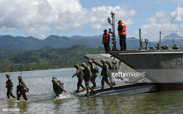 Philippine marines disembark fron their landing ship as security responders during a simulation of a disaster drill as part of the annual joint...