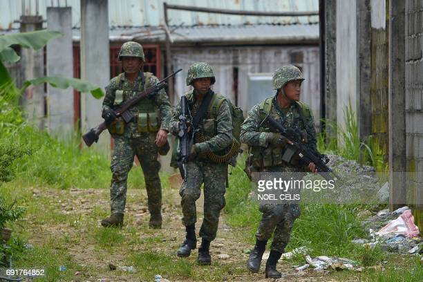 Philippine marines patrol a deserted area on their way to assault an Islamist militants' hideout in Marawi on the southern island of Mindanao on June...