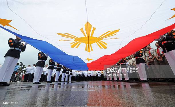 Philippine Marines raise the country's flag of the nation's 114th Independence Day celebrations in Manila on June 12 2012 The Philippines declared...