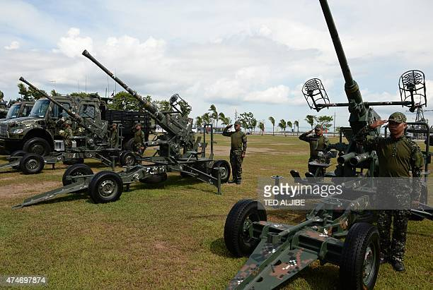 Philippine Marines stand next to newly acquired 40mm antiaircraft cannons displayed during the navy's founding anniversary celebration at a naval...