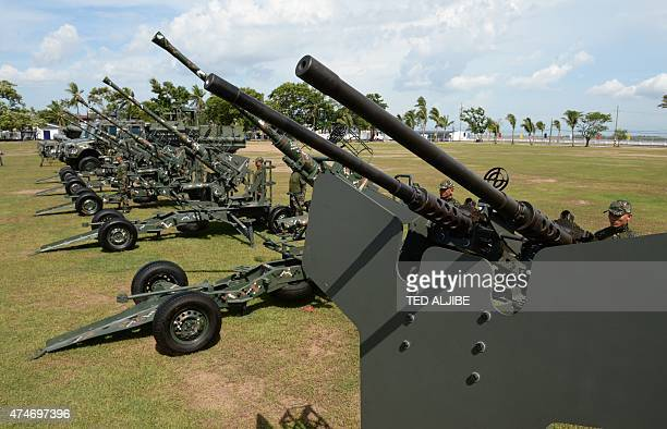 Philippine Marines stand next to twin 50 cal machine guns and newly acquired 40mm antiaircraft cannons displayed during the navy's founding...