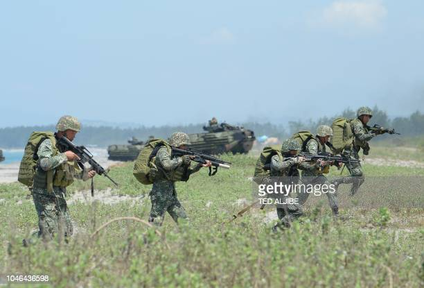 Philippine marines take position next to US marines Amphibious Assault Vehicles during an amphibious landing exercise at the beach of the Philippine...