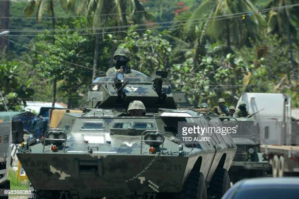 Philippine Marines travel along a highway in their armoured personnel carriers in Marawi on the southern island of Mindanao on June 20 2017 President...